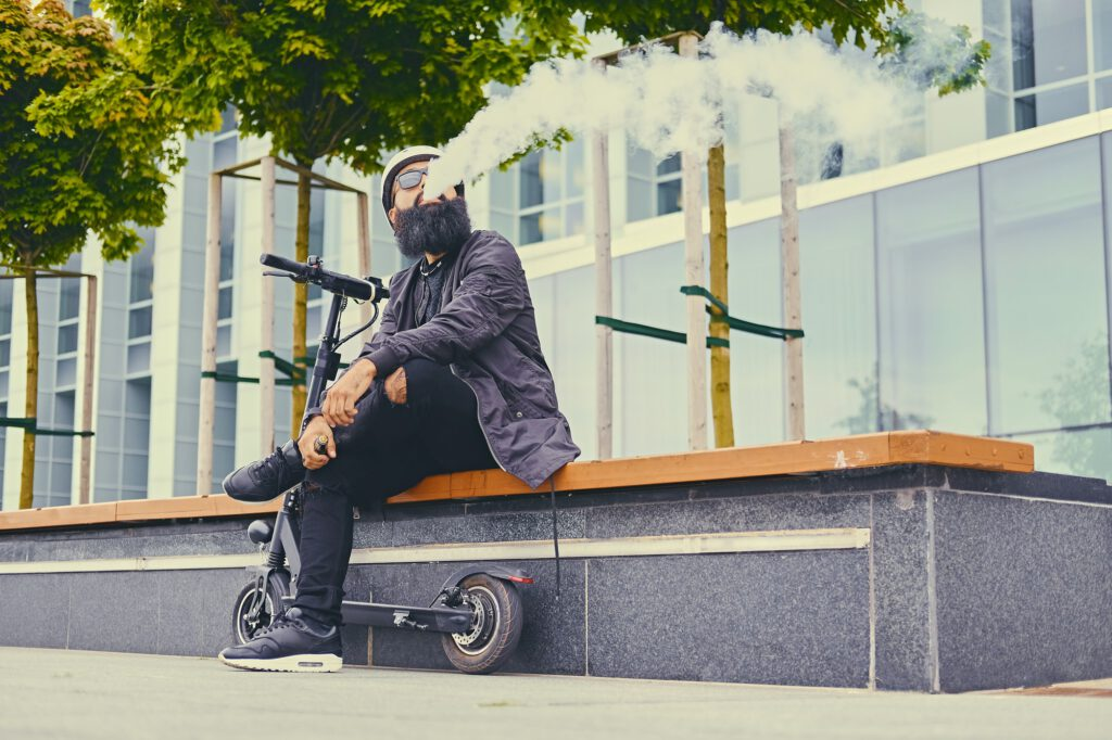 A man vaping after electric scooter.