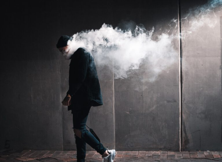 Young man vaping in the alley